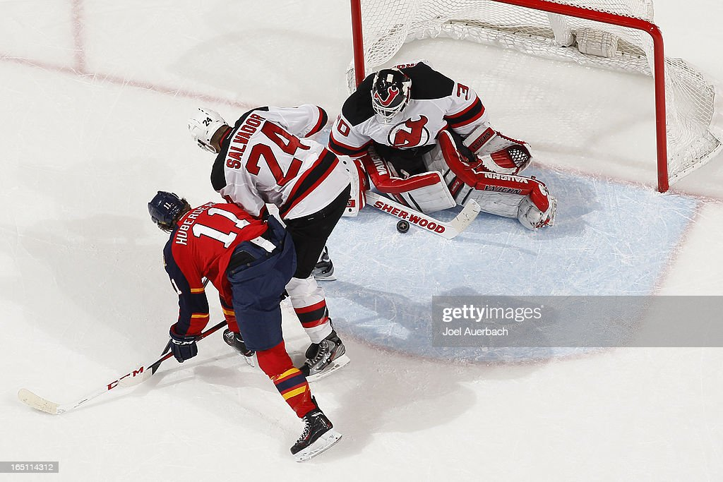 <a gi-track='captionPersonalityLinkClicked' href=/galleries/search?phrase=Bryce+Salvador&family=editorial&specificpeople=208746 ng-click='$event.stopPropagation()'>Bryce Salvador</a> #24 of the New Jersey Devils defends against <a gi-track='captionPersonalityLinkClicked' href=/galleries/search?phrase=Jonathan+Huberdeau&family=editorial&specificpeople=7144196 ng-click='$event.stopPropagation()'>Jonathan Huberdeau</a> #11 of the Florida Panthers as goaltender <a gi-track='captionPersonalityLinkClicked' href=/galleries/search?phrase=Martin+Brodeur&family=editorial&specificpeople=201594 ng-click='$event.stopPropagation()'>Martin Brodeur</a> #30 stops a shot in the second period at the BB&T Center on March 30, 2013 in Sunrise, Florida. The Panthers defeated the Devils 3-2 in overtime.