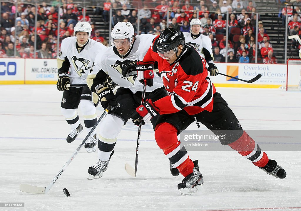 Bryce Salvador #24 of the New Jersey Devils plays the puck ahead of James Neal #18 of the Pittsburgh Penguins at the Prudential Center on February 9, 2013 in Newark, New Jersey.