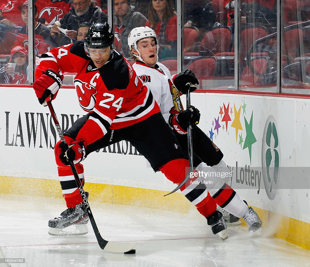 Bryce Salvador #24 of the New Jersey Devils plays the puck while being stick checked by Kyle Turris #7 of the Ottawa Senators during the game at the Prudential Center on February 18, 2013 in Newark, New Jersey.