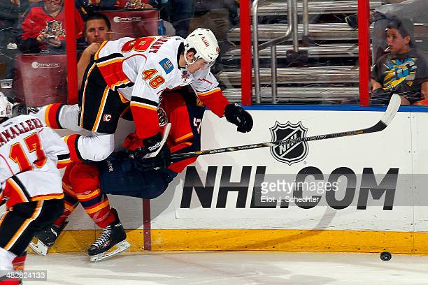 Bryce Van Brabant of the Calgary Flames collides with Colby Robak of the Florida Panthers at the BBT Center on April 4 2014 in Sunrise Florida