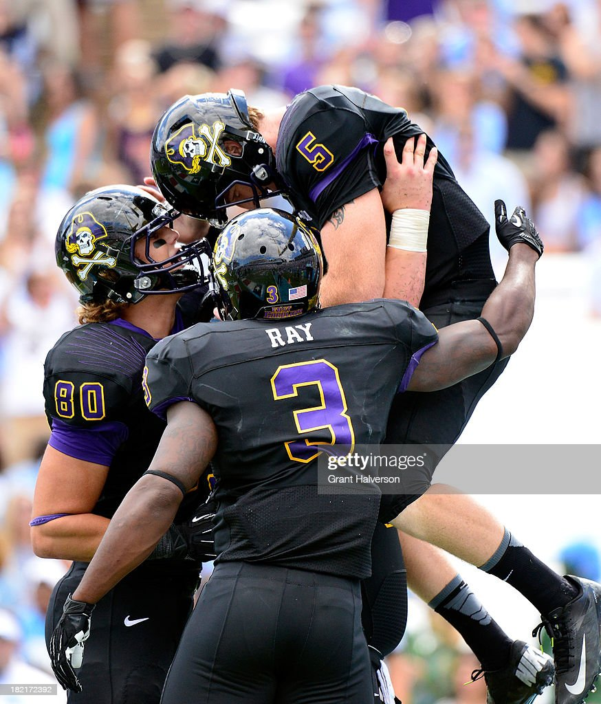 Bryce Williams #80 and Lance Ray #3 celebrate with teammate Shane Carden #5 of the East Carolina Pirates after Carden's touchdown against of the North Carolina Tar Heels during play at Kenan Stadium on September 28, 2013 in Chapel Hill, North Carolina. East Carolina won 55-31.