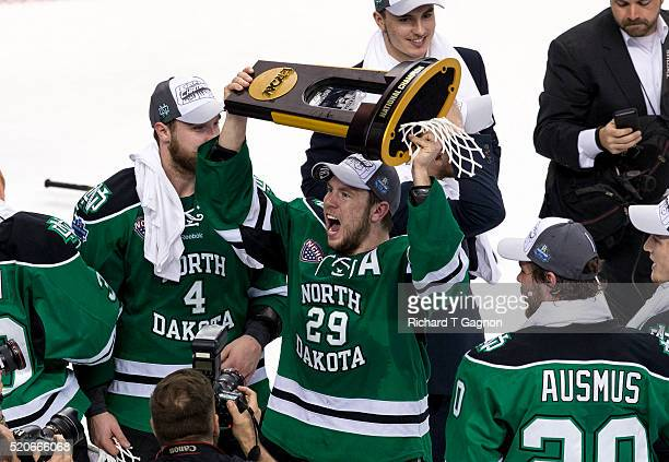 Bryn Chyzyk of North Dakota Fighting Hawks raises the championship trophy after defeating the Quinnipiac University Bobcats the 2016 NCAA Division I...