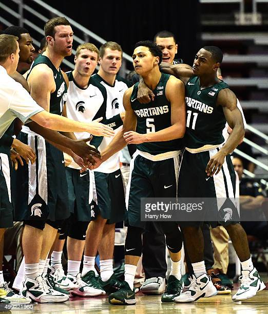 Bryn Forbes of the Michigan State Spartans celebrates his basket and a Providence Friars foul with Lourawls Nairn Jr #11 and the Spartans bench...