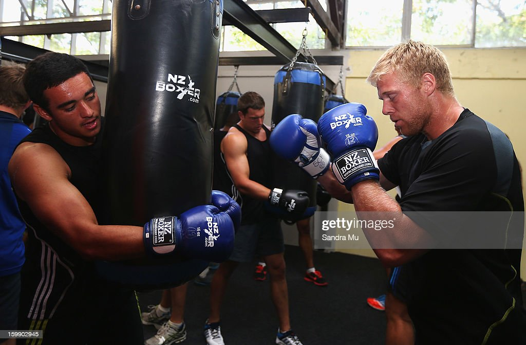 Bryn Hall (L) holds the bag for Baden Kerr during a Blues training session with Shane Cameron at Shane Cameron Fitness on January 23, 2013 in Auckland, New Zealand.