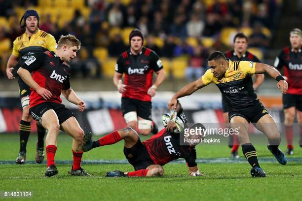 Bryn Hall of the Crusaders secures a loose ball under pressure from Ngani Laumape of the Hurricanes during the round 17 Super Rugby match between the...