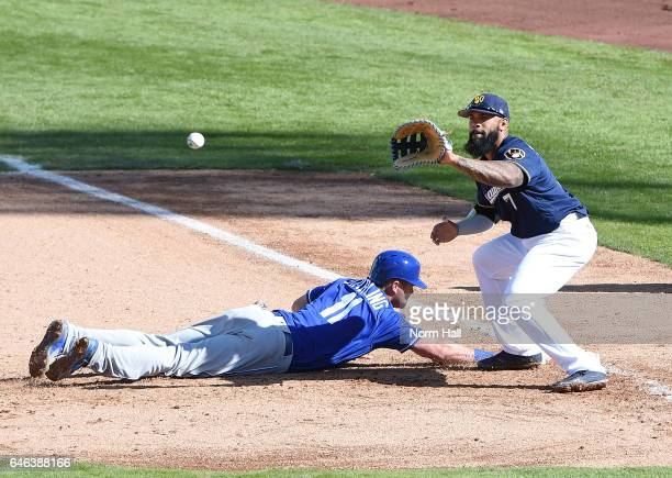 Bubba Starling of the Kansas City Royals dives safely back to first base as Eric Thames of the Milwaukee Brewers waits for the throw over from the...