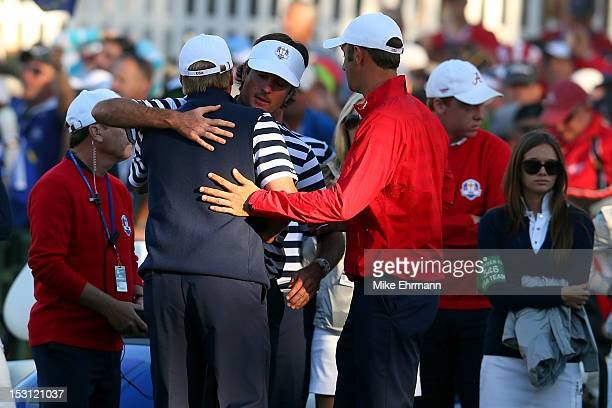 Bubba Watson and Dustin Johnson hug Steve Stricker near the 18th green during the Singles Matches for The 39th Ryder Cup at Medinah Country Club on...