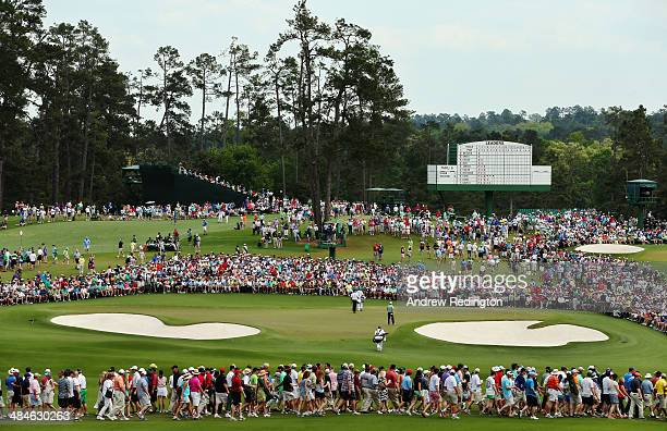 Bubba Watson and Jordan Spieth of the United States walk with their caddies to the second green during the final round of the 2014 Masters Tournament...