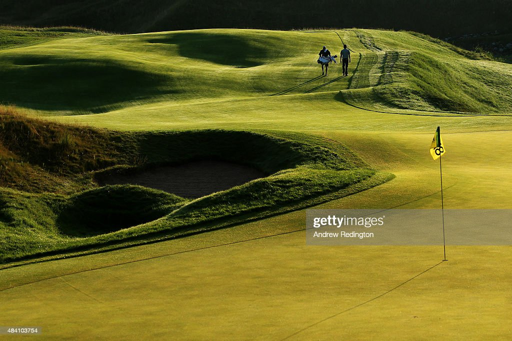 Bubba Watson of the United States and his caddie Ted Scott walks down the 18th fairway during the continuation of the weather-delayed second round of the 2015 PGA Championship at Whistling Straits on August 15, 2015 in Sheboygan, Wisconsin.