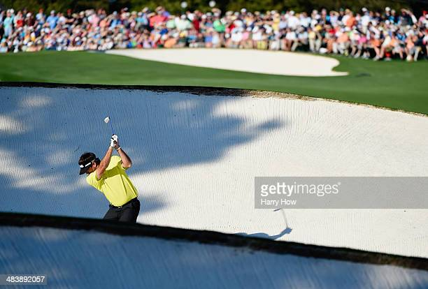 Bubba Watson of the United States hits a shot from a fairway bunker on the 18th hole during the first round of the 2014 Masters Tournament at Augusta...