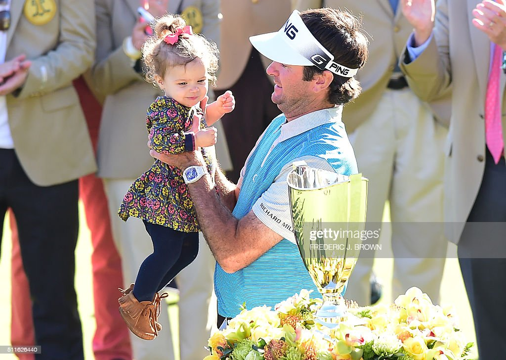 Bubba Watson of the United States lifts his daughter Dakota before the championship trophy on the final day at the 2016 Northern Trust Open on...