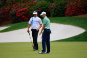 Bubba Watson of the United States walks across the 13th green alongside Jordan Spieth of the United States during the final round of the 2014 Masters...