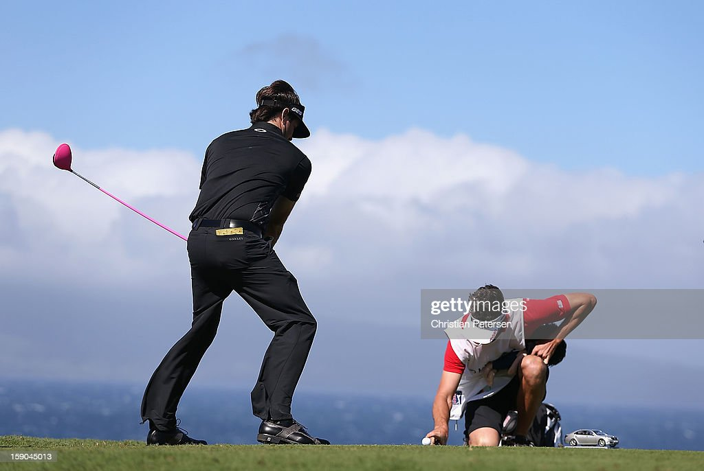 Bubba Watson pretends to tee off as his caddie Ted Scott holds a finger on the ball to keep it from blowing away on the 10th hole during the replay of the first round of the Hyundai Tournament of Champions at the Plantation Course on January 6, 2013 in Kapalua, Hawaii.