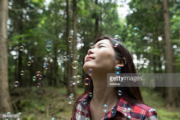Bubbles and cute girl in the forest.