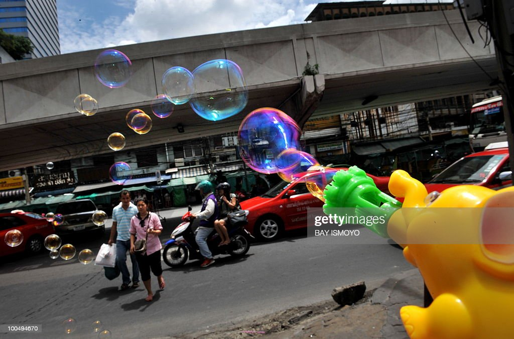 Bubbles float past a couple crossing the street in downtown Bangkok on May 25, 2010. Thailand's economy grew at breakneck pace early this year but the deadly unrest that began in March will clip the full-year performance by 1.5 percentage points, officials said. AFP PHOTO / Bay ISMOYO