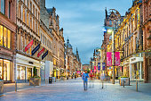 Stock photograph of people walking on Buchanan Street in downtown Glasgow, Scotland, UK at twilight. Buchanan Street forms the central stretch of Glasgow's famous shopping district.
