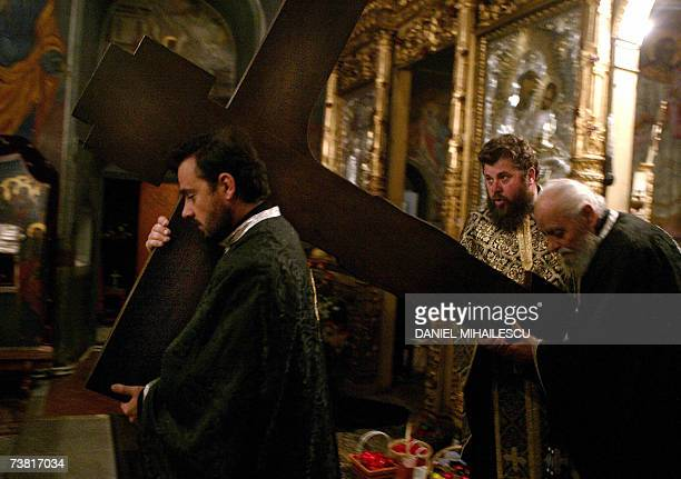 Romanian Orthodox priests carry a wooden cross to be placed in the middle of the church at the Pasarea monastery 20 kms from Bucharest on the day...