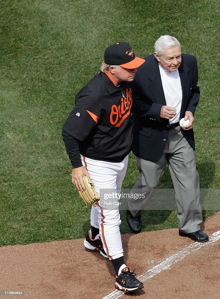 Buck Showalter #26 manager of the Baltimore Orioles talks with former Orioles manager Earl Weaver (R) after Weaver threw out the ceremonial first pitch before the start of their game against the Detroit Tigers during opening day at Oriole Park at Camden Yards on April 4, 2011 in Baltimore, Maryland.