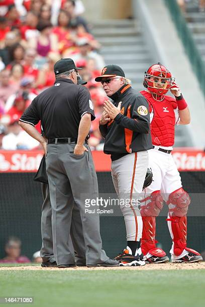 Buck Showalter manager of the Baltimore Orioles with home plate umpire Angel Campos and second base umpire Dale Scott during the game against the Los...