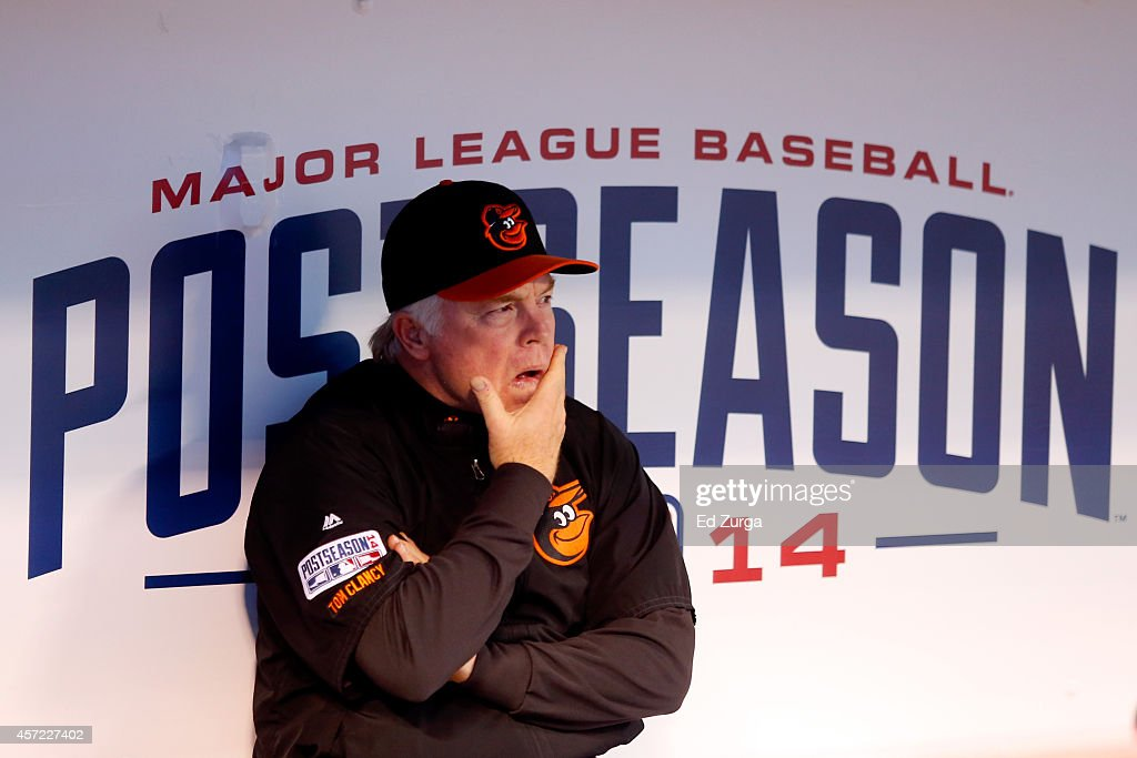 Buck Showalter #26 of the Baltimore Orioles looks on from the dugout prior to Game Three of the American League Championship Series against the Kansas City Royals at Kauffman Stadium on October 14, 2014 in Kansas City, Missouri.