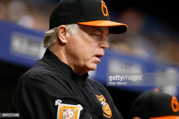 Buck Showalter of the Baltimore Orioles stands just outside the dugout as he waits to hear an explanation from umpires after Manny Machado popped...