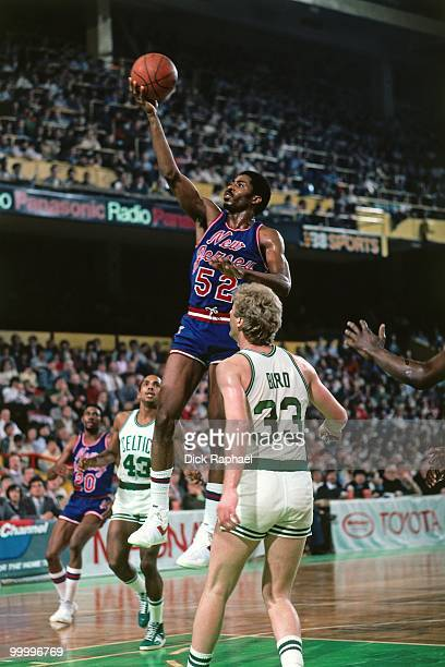 Buck Williams of the New Jersey Nets shoots a layup against Larry Bird of the Boston Celtics during a game played in 1983 at the Boston Garden in...