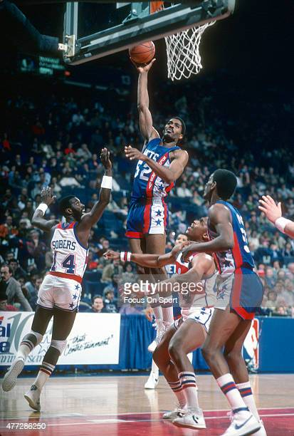 Buck Williams of the New Jersey Nets shoots over Ricky Sobers of the Washington Bullets during an NBA basketball game circa 1984 at the Capital...