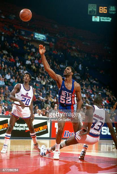 Buck Williams of the New Jersey Nets shoots over Terry Catledge of the Washington Bullets during an NBA basketball game circa 1986 at the Capital...