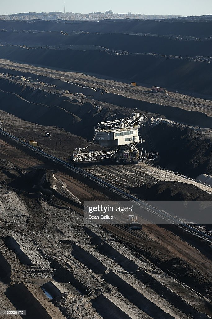 A bucket excavator six storeys tall mines lignite coal at the Jaenschwalde open-pit coal mine on October 31, 2013 near Jaenschwalde, Germany. According to plans by Swedish energy conglomerate Vattenfall and approved by the Brandenburg state legislature, at least five local communities are to be raized and their inhabitants compensated and relocated in order to make way for the expansion of the mine. Energy policy and the role of coal is a heated topic at the moment in coalition negotiations between the Social Democrats (SPD) and Christian Democrats (CDU) currently taking place in Berlin.
