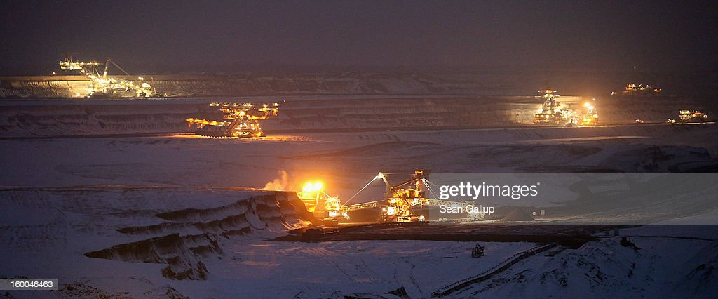 Bucket excavators stand illuminated at the snow-covered Vereinigtes Schleenhain open-pit coal mine on January 25, 2013 near Deutzen, Germany. The mine, which is operated by Mibrag, is one of several across eastern Germany that produce lignite coal for local electricity production.