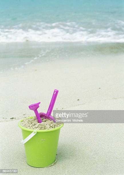 Bucket filled with sand and beach toys on beach