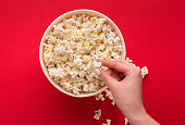 Hand taking popcorn from classic striped bucket on red background. Hot corn scattered from paper box, copy space. Fast food and movie snack, top view