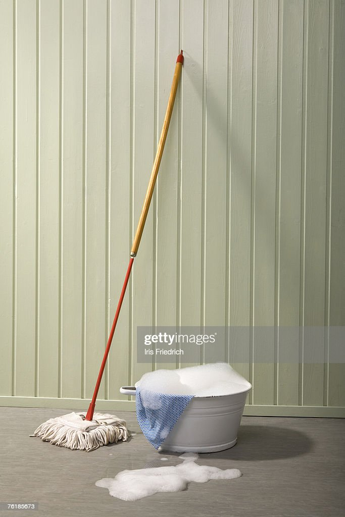 A bucket of soapy water and a mop : Stock Photo