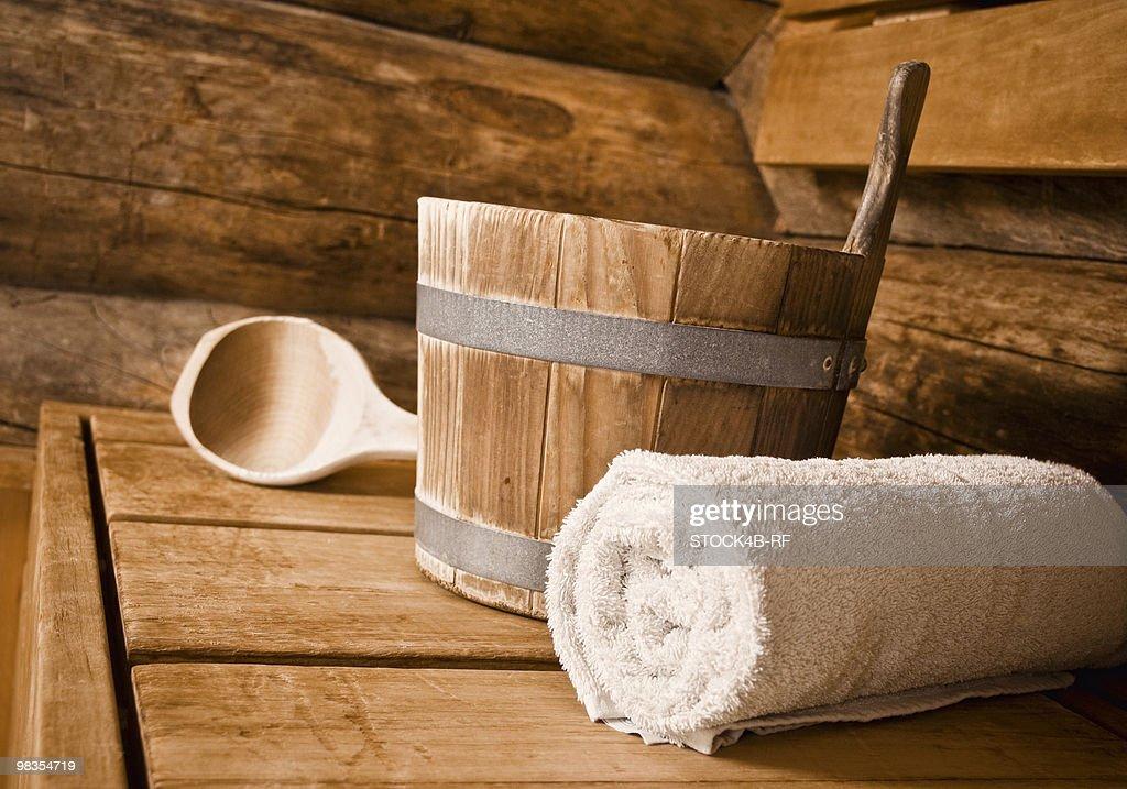 Bucket, towel and wooden spoon in sauna : Stock Photo