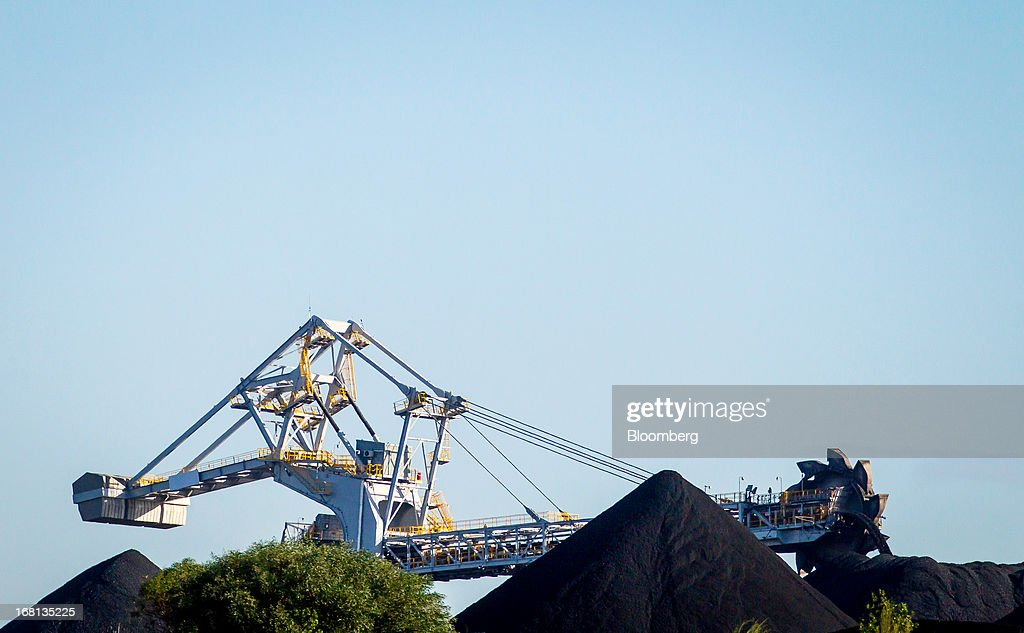 A bucket wheel reclaimer operates behind stockpiles of coal at the Newcastle Coal Terminal in Newcastle, north of Sydney, Australia, on Friday, May 3, 2013. Australia's forecast mining tax revenue has been downgraded, underscoring the 'grave' budget decisions facing Prime Minister Julia Gillard as the strength of the local dollar squeezes trade-exposed businesses. Photographer: Ian Waldie/Bloomberg via Getty Images