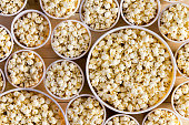 Overhead view of different sized buckets full of freshly made popcorn for everyone filling the frame