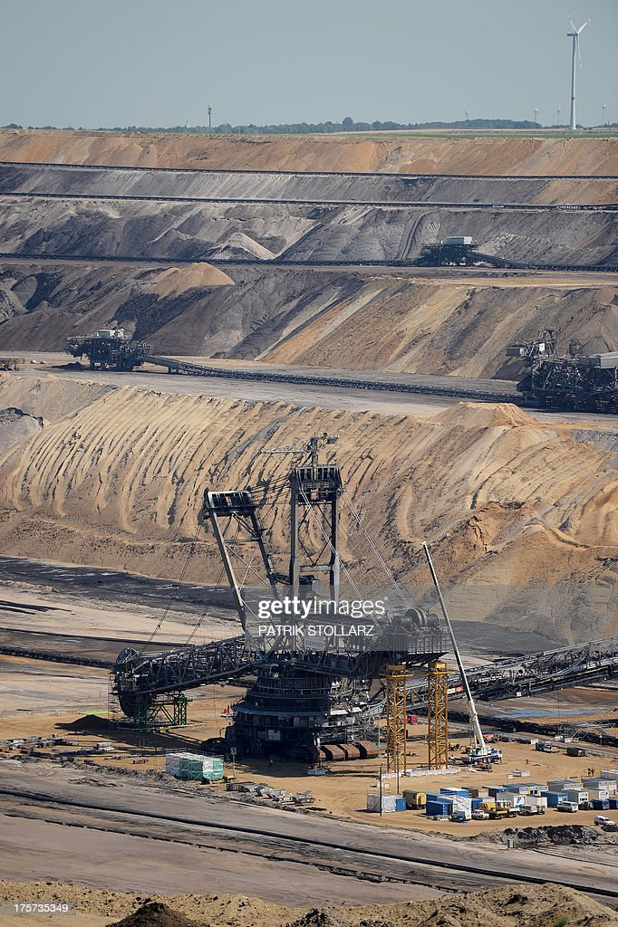 A bucket-wheel excavator extracts coal from the brown coal open cast mine Garzweiler on August 5, 2013 in Immigrath, western Germany. The small town Immerath and surrounding towns will be wiped off the map to allow energy giant RWE enlarge the huge open pit mine Garzweiler. AFP PHOTO / PATRIK STOLLARZ
