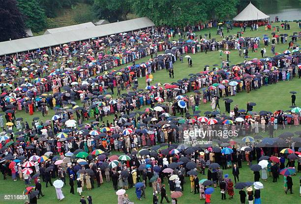 Buckingham Palace Garden Party Continues Despite Rainy Weather Sheltering Under Umbrellas The Guests Form Rows Through Which Members Of The Royal...