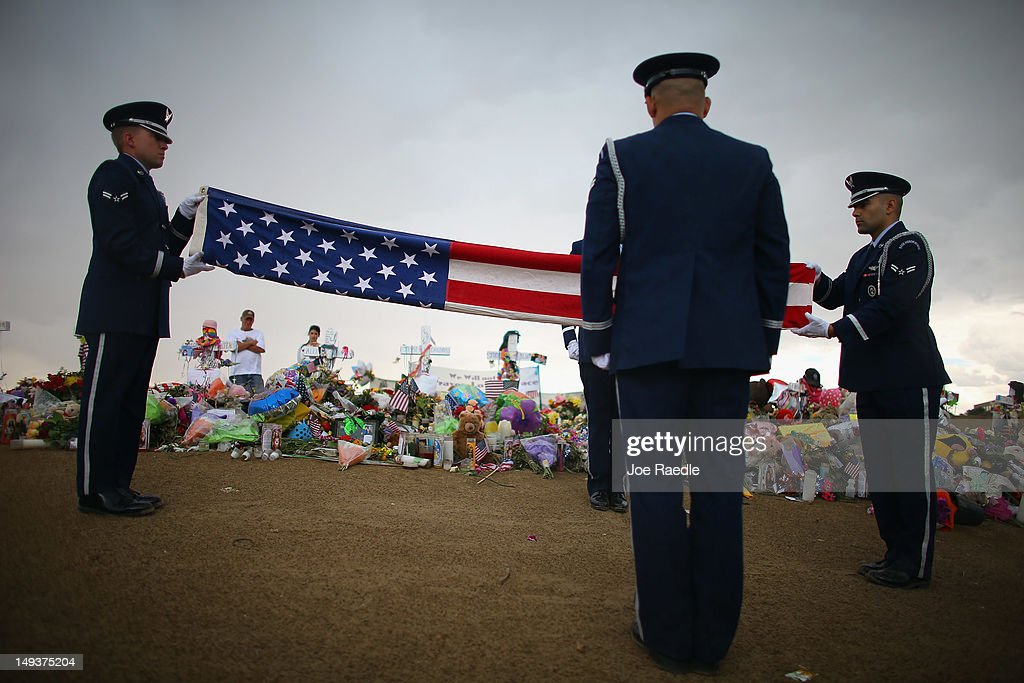Buckley Air Force base Mile High Honor Guard folds an American flag at a memorial setup across the street from the Century 16 movie theatre on July 27, 2012 in Aurora, Colorado. Twenty-four-year-old James Holmes is suspected of killing 12 and injuring 58 others July 20 during a shooting rampage at a screening of 'The Dark Knight Rises' in Aurora, Colorado.