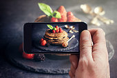 Man photographing wit his phone buckwheat pancakes with fruit
