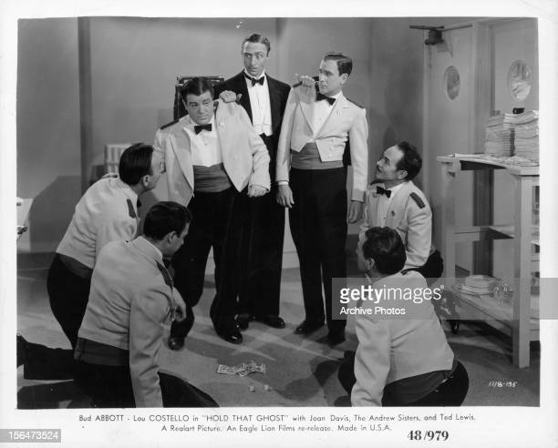 Bud Abbott and Lou Costello are being held by the shoulder of their jackets by a man in a tuxedo in a scene from the film 'Hold That Ghost' 1941