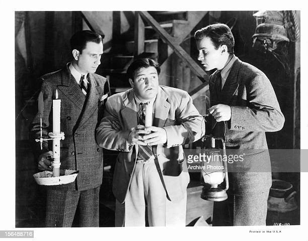 Bud Abbott Lou Costello and Richard Carlson hold lanterns in a scene from the film 'Hold That Ghost' 1941