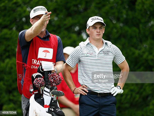 Bud Cauley of the United States listens to his caddie Mike Bestor on the ninth tee during the first round of the Travelers Championship golf...