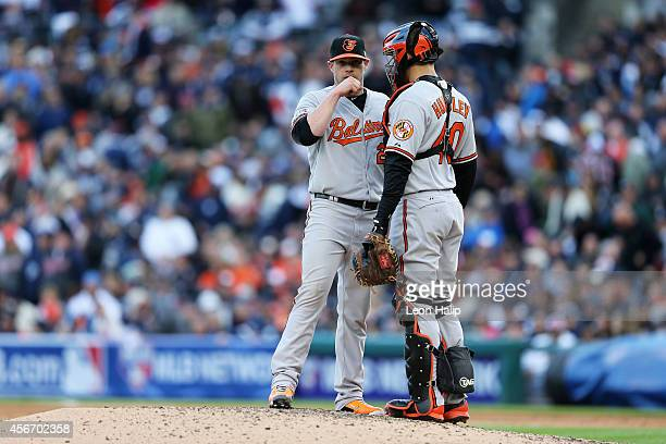 Bud Norris talks to Nick Hundley of the Baltimore Orioles on the mound in the fifth inning against the Detroit Tigers during Game Three of the...