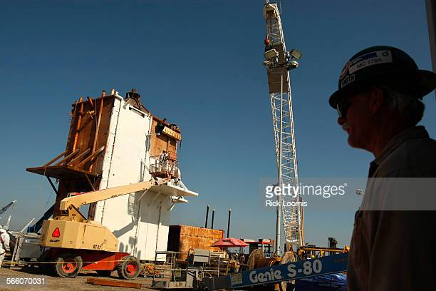 Bud Parker a logistics coordinator for Walsh Offshore Personnel watches as round–the–clock work continues on the construction of a large pollution...
