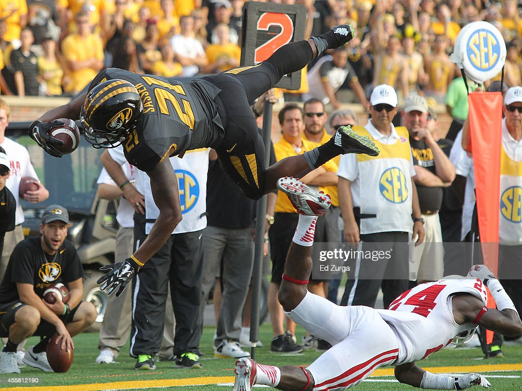 Bud Sasser #21 of the Missouri Tigers leaps over cornerback Tim Bennett #24 of the Indiana Hoosiers as he comes up short of the goal line in the fourth quarter at Memorial Stadium on September 20, 2014 in Columbia, Missouri. Indiana won 31-27.