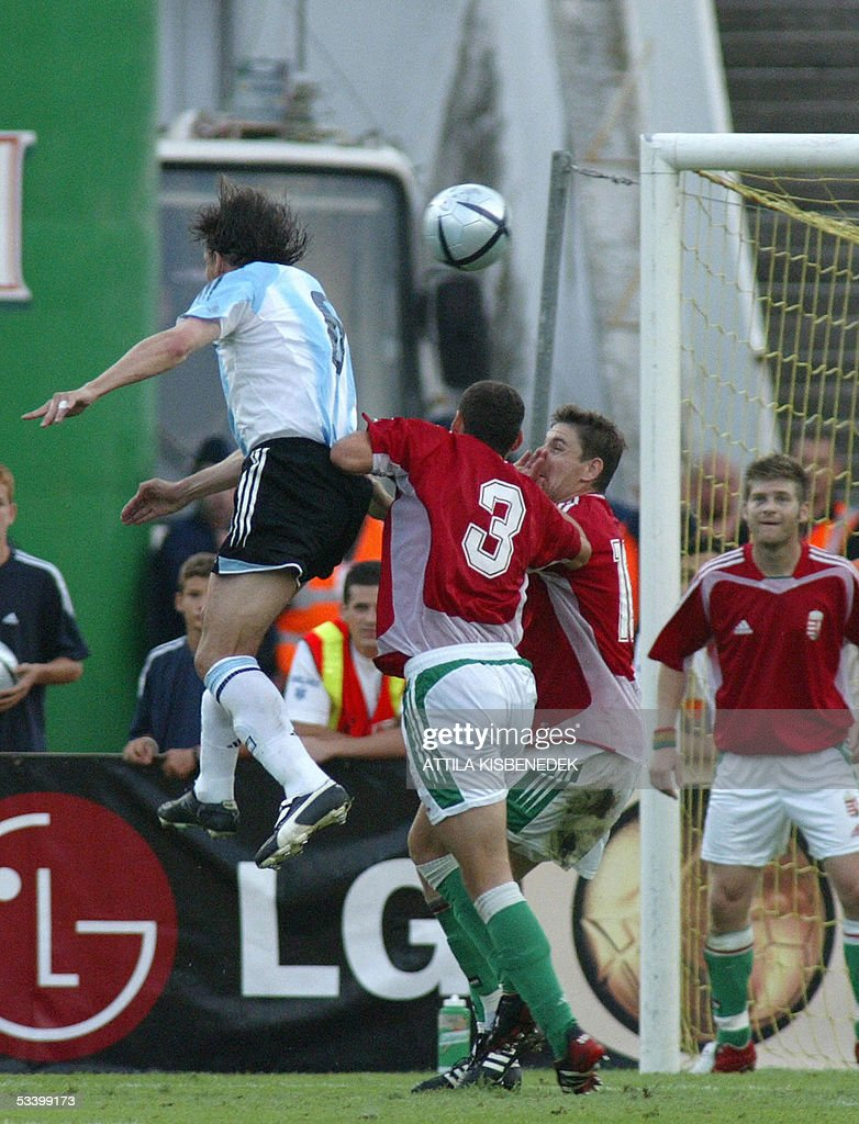 Accompanied by Hungarian players, (L to R), Vilmos Vanczak, Zoltan Gera and Zoltan Boor, Argentine Gabrela Heinze heads the ball and scores the second goal for his team in 'Puskas' stadium in Budapest 17 August 2005 during a friendly match between their national teams.