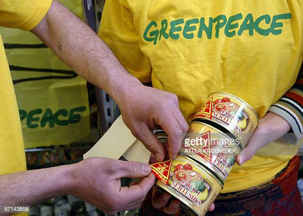 Activists of the International environmental watchdog Greenpeace put stickers on cans containing food with genetically modified ingredients during a...