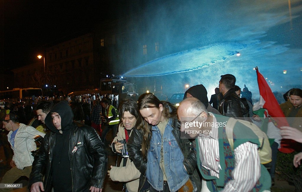 Anti-government demostrators flee from water cannon with blue-coloured water on the eve of the anniversary of the 1848 Revolution and Freedom fight on Andrassy Avenue in Budapest 15 March 2007. The Hungarian police were out in force to ensure order amid fears of a resurgence of street violence on the national day.