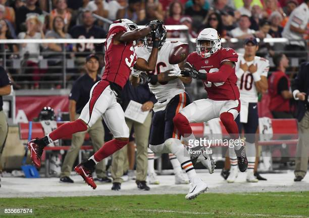 Budda Baker and Tramon Williams of the Arizona Cardinals break up a pass intended for Zach Miller of the Chicago Bears during the first half at...